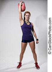 Young attractive female doing kettle bell exercise o