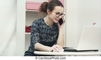 Young attractive female fashion designer using computer laptop and talking on mobile phone call in manufacturing office studio