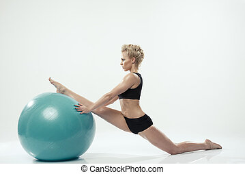 Young attractive female fitness model performing a twine on ball