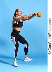 young attractive female sportswoman doing kettle bell exercise on blue background.