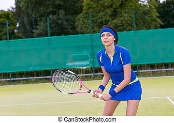 Young attractive female tennis player during the game in the morning