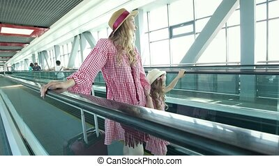 Young attractive female traveler rises on escalator at the...