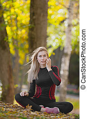 Young attractive fitness female sitting cross-legged at workout in autumn park, straightens her waving in the wind hair