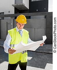 young attractive foreman worker supervising building blueprints outdoors wearing construction helmet