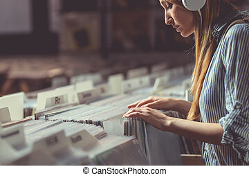 Young attractive girl browsing records