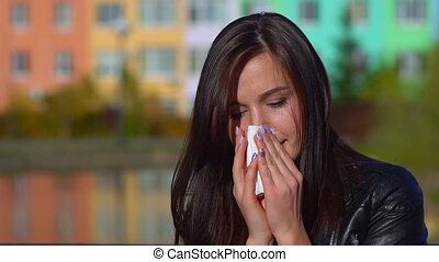 Young attractive girl, caught a cold on the street, wipes her nose with a napkin.