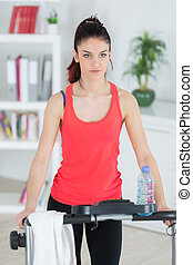 young attractive girl exercise at home on step machine