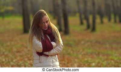 Young attractive girl frozen in the autumn Park, warm hands.