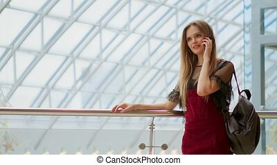 Young attractive girl goes shopping in mall, talking on...