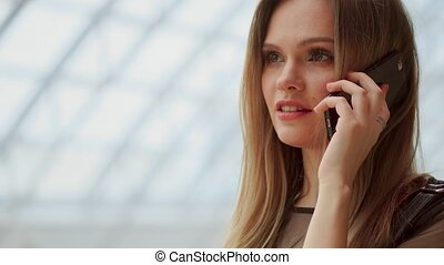 Young attractive girl goes shopping in mall, talking on phone, shopping concept, fashion concept, communication concept.