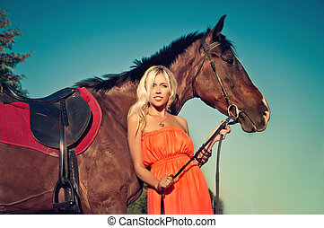 young attractive girl holding a horse's reins