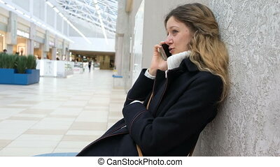 Young attractive girl in a coat talking on a cell phone at the Mall. Tired shopping at the village to rest and to talk.