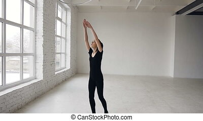 Young attractive girl in black body performs training a gymnastics exercise with a hoop in the gymnastic school on white background