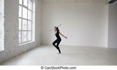 Young attractive girl in black body training a gymnastics exercise with a hoop in the sports school at white background
