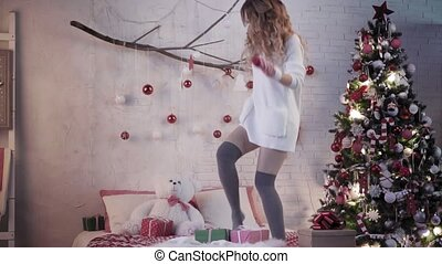 Young attractive girl in mittens dancing on a bed near a...