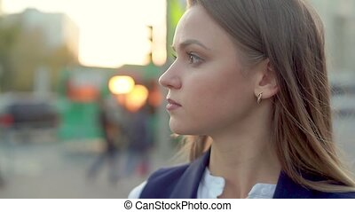 Young attractive girl in the center of the city, looking into the distance at sunset in the evening.