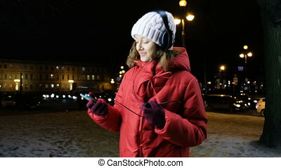 Young attractive girl listening to music on headphones in a smartphone in the evening in winter.