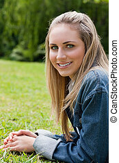 Young attractive girl looking at the camera while lying on the grass in a public garden