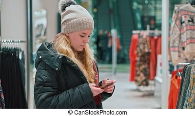 Young attractive girl looks into the smartphone. She's in a clothing store, a mall