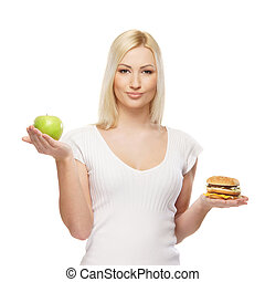Young attractive girl making choice between healthy and harmful food