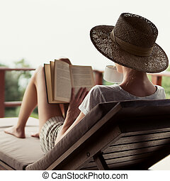 Young attractive girl reads a book on balcony.