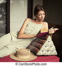 Young attractive girl reads a book on sofa