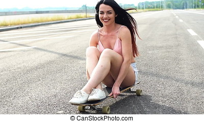 Young attractive girl riding longboard, slow motion.