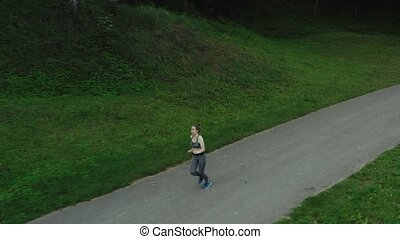 Young attractive girl running in city park. Woman running in...