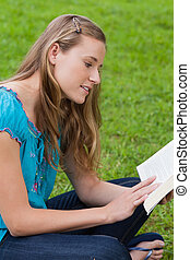 Young attractive girl sitting down on the grass in a park while reading a book