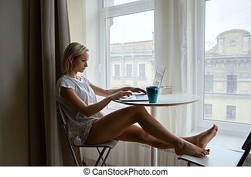 Young attractive girl sitting near big window with coffee and working on laptop.