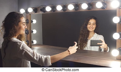 Young attractive girl uses a smartphone for selfie.