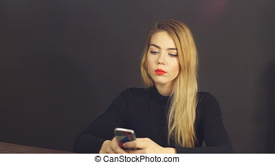 Young attractive girl uses a smartphone.