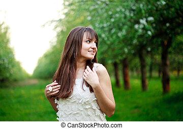 Young attractive girl walking in the garden