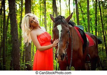 young attractive girl with horse in the forest