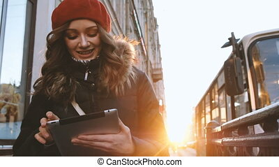Young attractive girl with tablet in the sunset in the city. lifestyle portrait of young female using smart phone tablet for social media networking