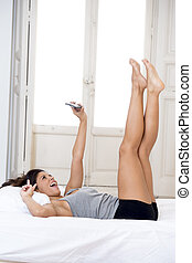 young attractive hispanic woman in bed taking selfie photo with mobile phone smiling happy