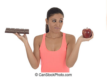 young attractive hispanic woman in fitness top holding apple fruit and chocolate bar in her hands