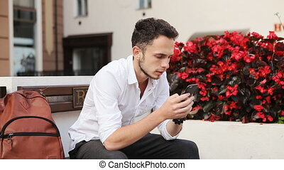 Young attractive male in his 20s sitting on a bench and...