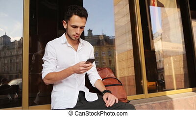 Young attractive male in white shirt texting on his smartphone outdoors. Close-up porttrait of man scrolling his mobile phone.