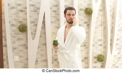 Young attractive man in white robe resting in a luxury Spa...