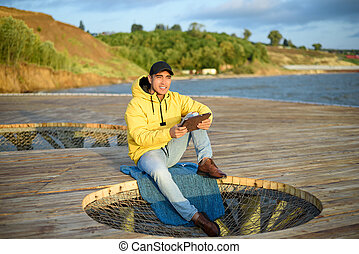 Young attractive man in yellow jacket and black cap sitting on the pier with tablet looking at dawn