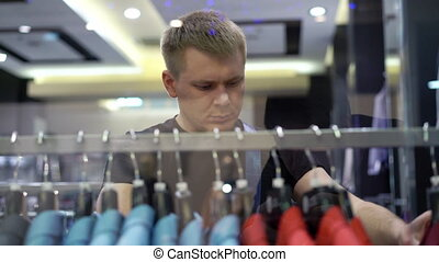 Young attractive man looking at shop window with men's suits...