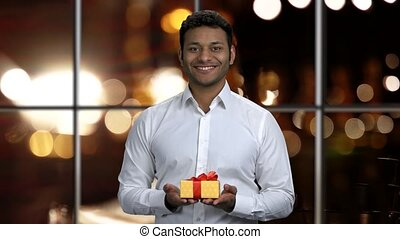 Young attractive man offering gift box. Happy businessman ...