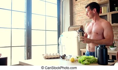 man preparing a protein cocktail in the kitchen