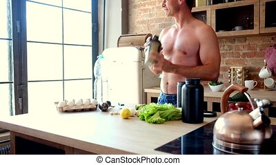 man Shaking a protein cocktail in the kitchen - Young...