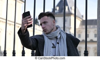 Young attractive man taking selfie photo outdoor in city