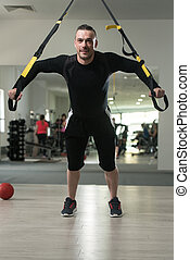 Young Attractive Man Training With Trx Fitness Straps -...