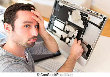 Young attractive man trying to repair computer
