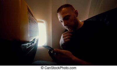 Young attractive man uses smartphone inside the airplane next to window. Handsome male traveling by air.