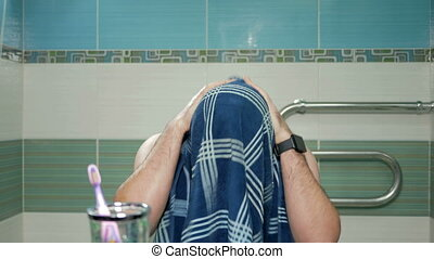 Young attractive man wipes his face with a towel and hands in the bathroom after a shower at the hotel. He looks into the camera in the mirror.